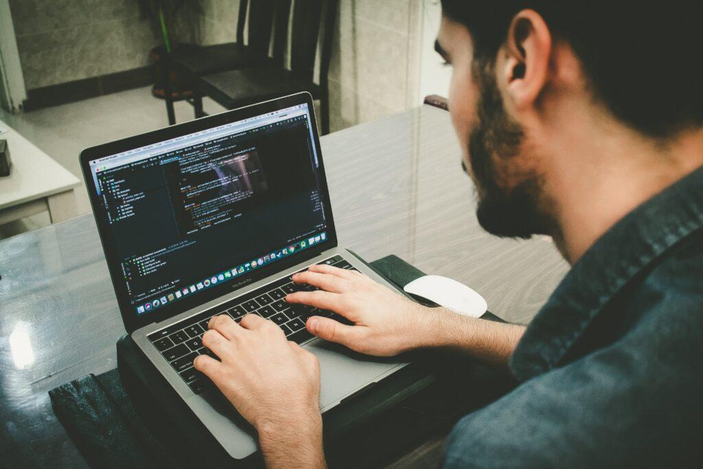 man programming using laptop